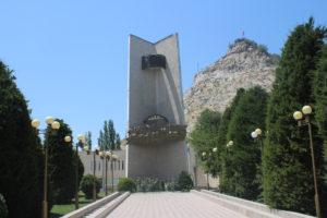 Monumento con alle spalle una delle cinque vette del Sulayman-Too